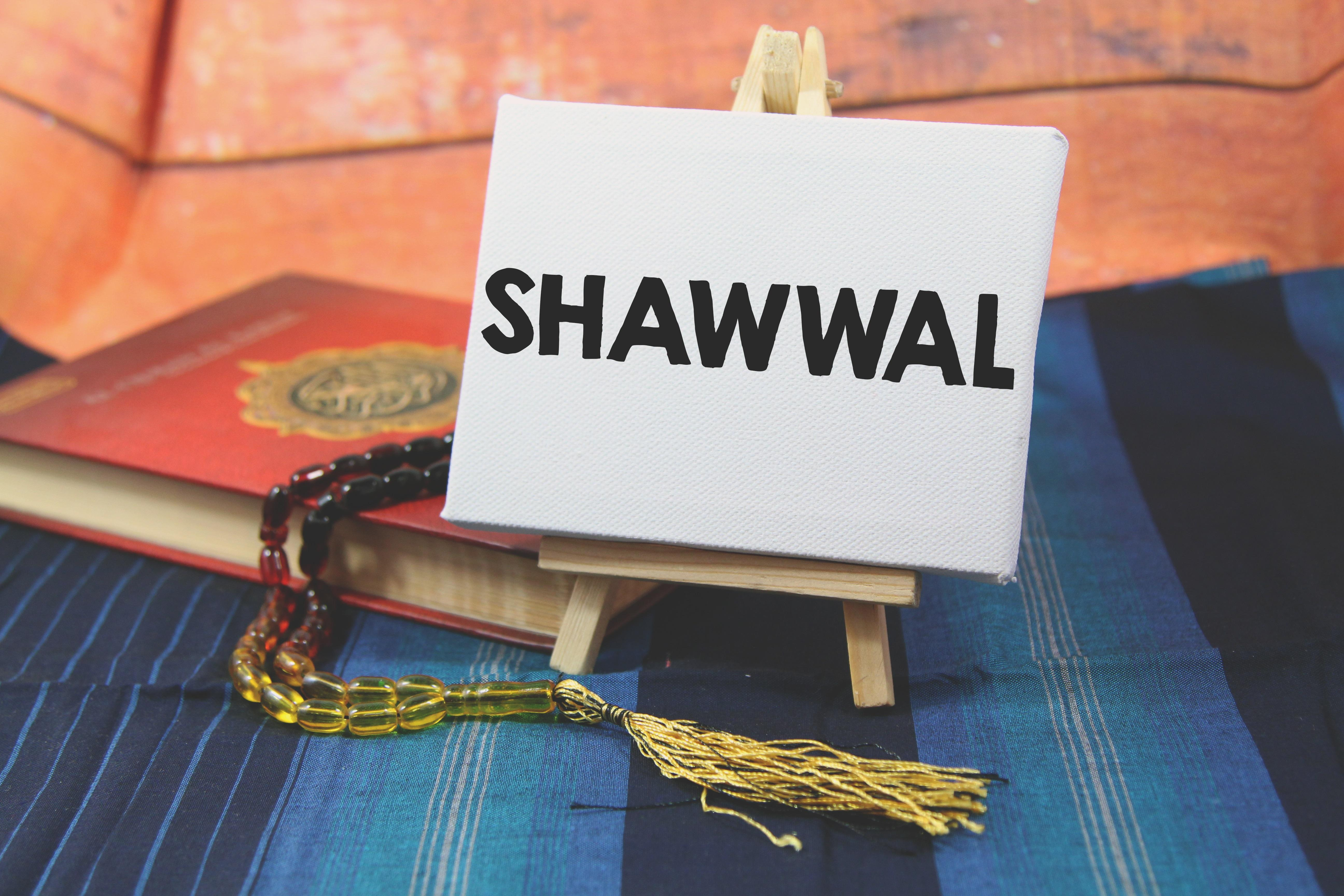 Quran and Islamic Rosary placed behind a stand up board with Shawwal on it